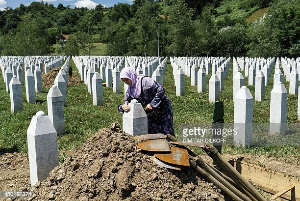 An elderly Bosnian woman cleans the tombstone on the grave of a relative at the Potocari Memorial Center near the eastern Bosnian town of Srebrenica...