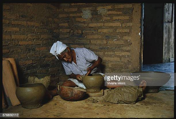 An elderly Brazilian woman sculpts a clay pottery bowl in the village of Itacima The area is known for its locally produced arts and crafts