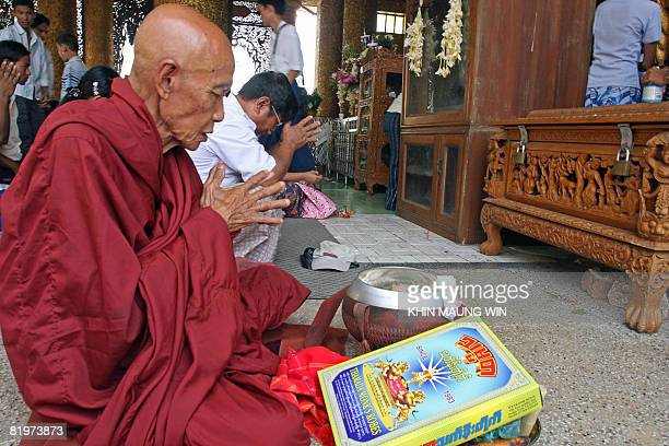 An elderly Buddhist monk reads religious verses at the famous Shwedagon Pagoda in downtown Yangon as they recite religious verses on July 17 2008 to...