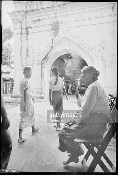An elderly Burmese woman intently puffs away at her cheroot