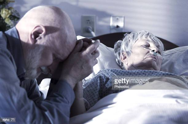 an elderly caucasain gentleman visits and prays over his wife as she tries to recover from an illness - old woman in sick bed stock photos and pictures
