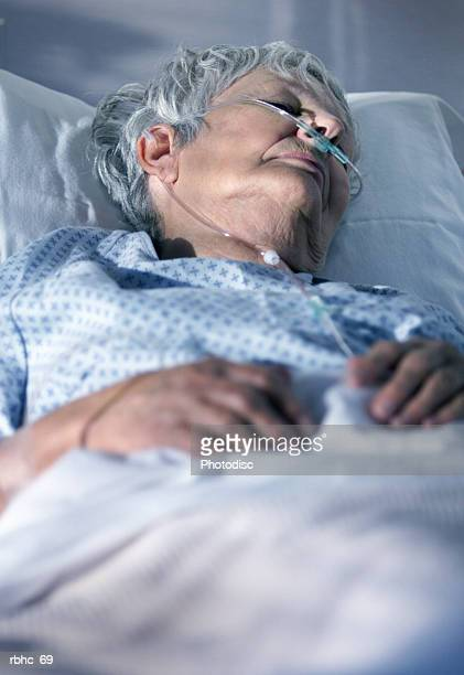 an elderly caucasain woman lays in a hospital bed as she tries to recover from an illness