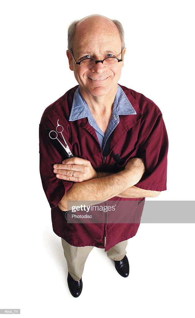 an elderly caucasian barber folds his arms and holds his scissors as he looks up at the camera : Foto de stock