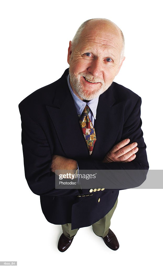 an elderly caucasian business man folds his arms and smiles as he looks up at the camera : Foto de stock