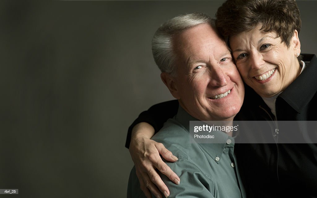 an elderly caucasian couple smile brightly as they hug each other : Foto de stock