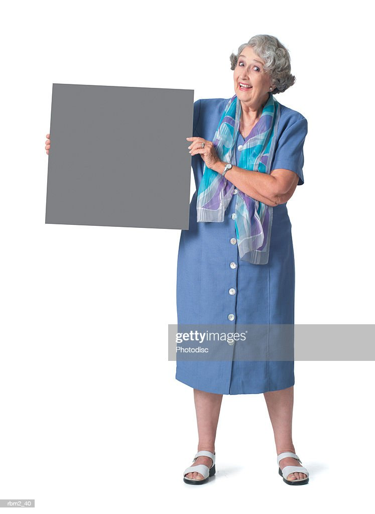 an elderly caucasian female in a blue dress holds a square sign to her side and smiles : Stockfoto