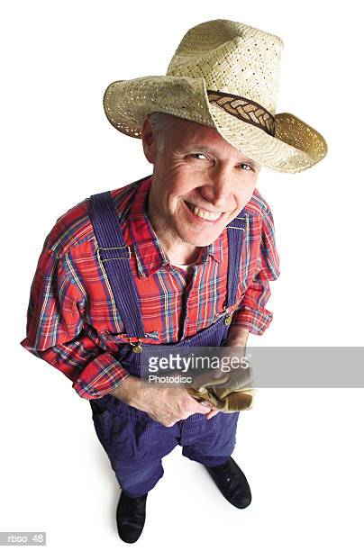 an elderly caucasian male farmer in overalls and a cowboy hat smiles as he looks up at the camera