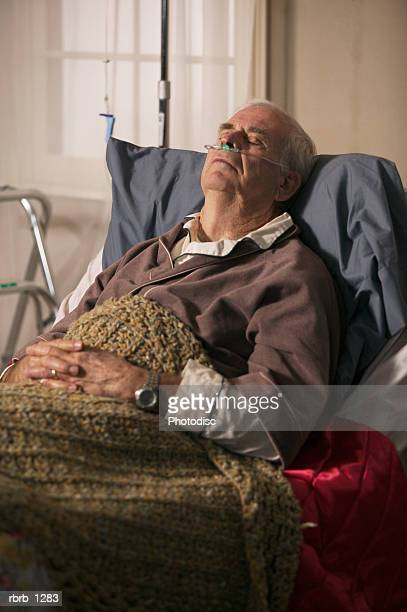 an elderly caucasian man in a brown robe lays in bed and rests with the aid of an oxygen tube