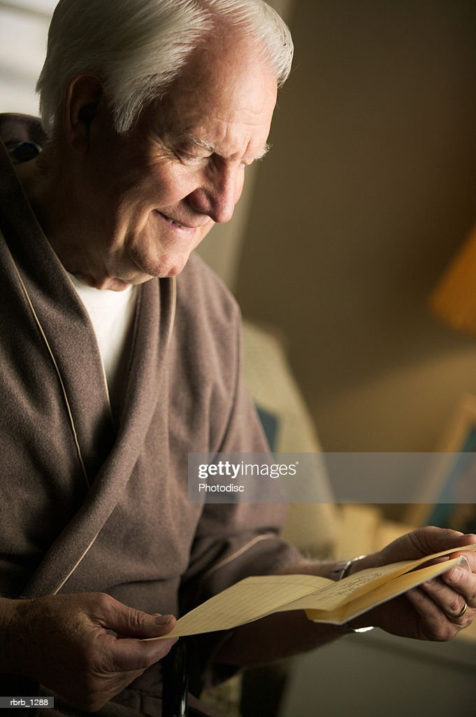 an elderly caucasian man in a brown robe sits and reads a letter in his bedroom : Stockfoto