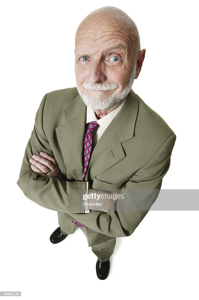 an elderly caucasian man with a beard in a green suit folds his arms and smirks up at the camera : Foto de stock