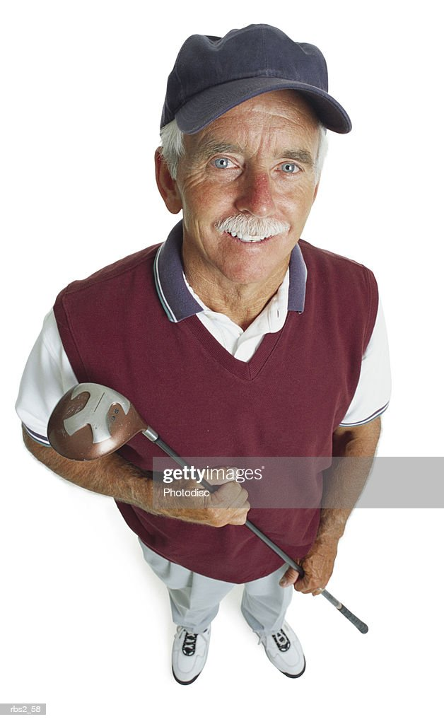 an elderly caucasian man with a white mustache is wearing a blue hat and a maroon vest as he holds his golf club and smiles up at the camera : Foto de stock
