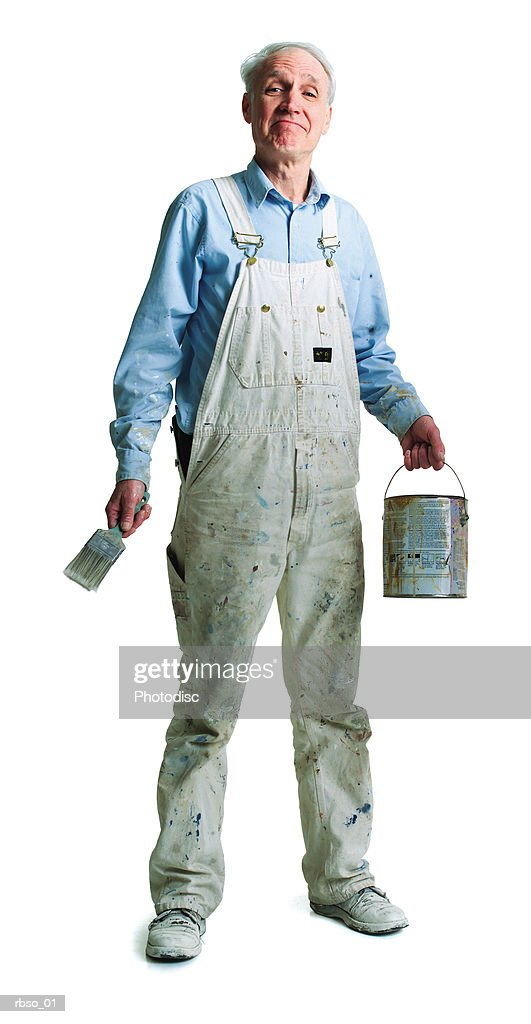an elderly caucasian painter stands with his brush and paint bucket : Foto de stock