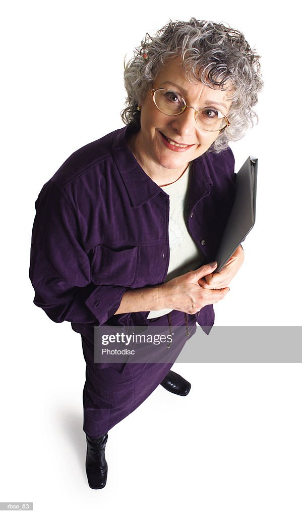 an elderly caucasian school teacher holds her notebook and smiles as she looks up at the camera : Stockfoto