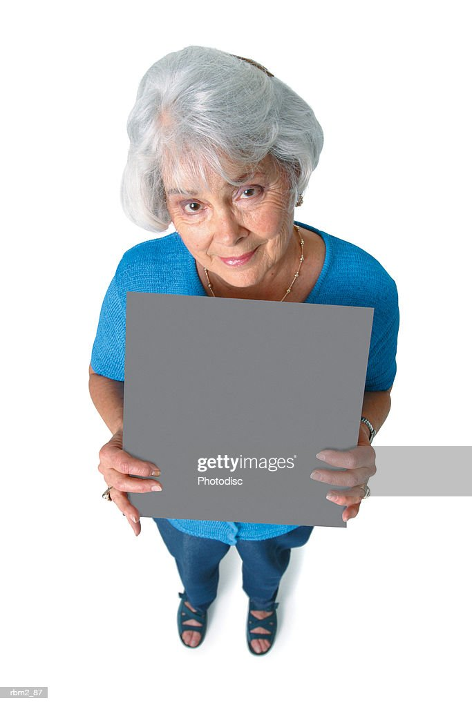 an elderly caucasian woman in a blue shirt holds a sign in front of her as she smiles up at the camera : Stockfoto