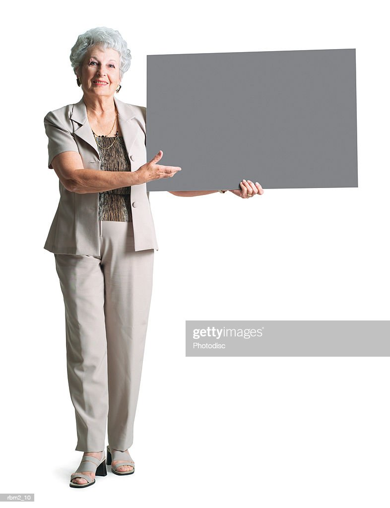 an elderly caucasian woman in a tan pant suit holds a sign to her side and smiles : Stockfoto