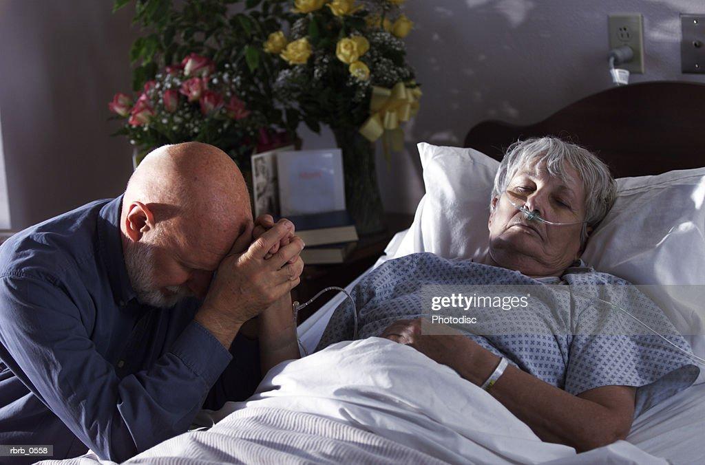 an elderly caucasian woman lies sick in a hospital bed as