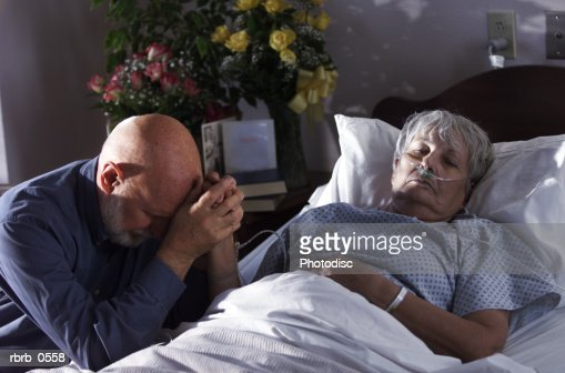 an elderly caucasian woman lies sick in a hospital bed as