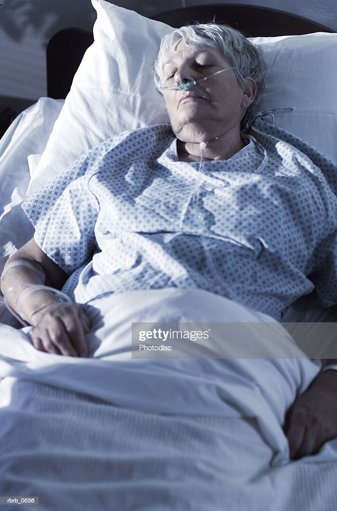 an elderly caucasian woman lies sick in a hospital bed : Stockfoto