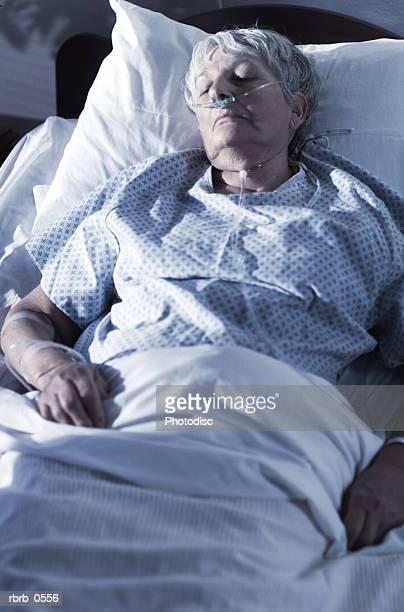 an elderly caucasian woman lies sick in a hospital bed