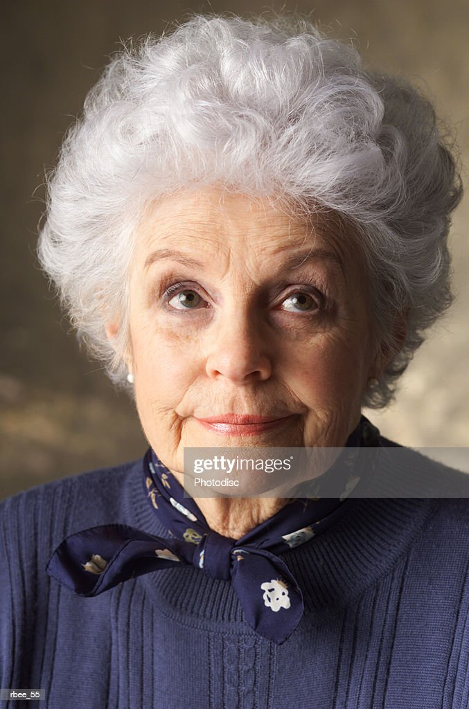 an elderly caucasian woman with curly white hair is wearing a blue sweater and looking smugly upward : Stockfoto