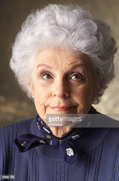 an elderly caucasian woman with curly white hair is wearing a blue sweater and looking smugly upward - one senior woman only stock pictures, royalty-free photos & images