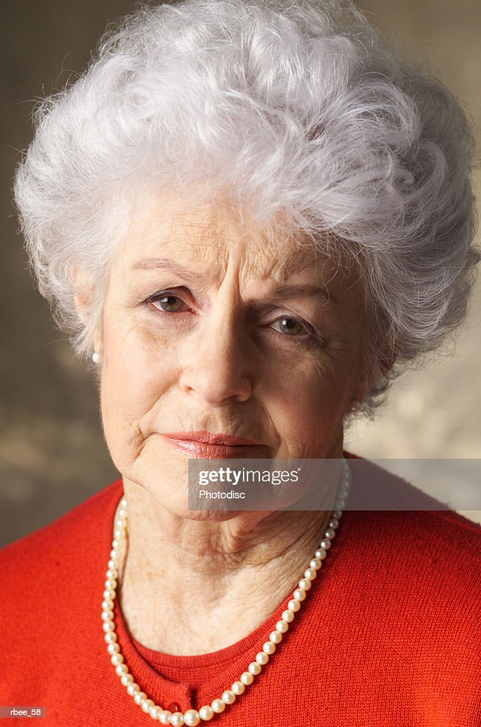 an elderly caucasian woman with curly white hair is wearing a red shirt and has an expression of sadness : Stockfoto