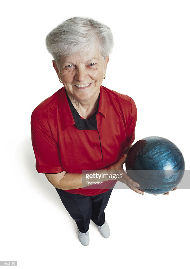an elderly caucasian woman with white hair is wearing a red bowling shirt and holding her blue bowling ball as she looks up at the camera smiling : Foto de stock