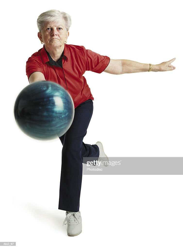 an elderly caucasian woman with white hair runs toward the camera wearing a red shirt and about to throw her blue bowling ball : Foto de stock