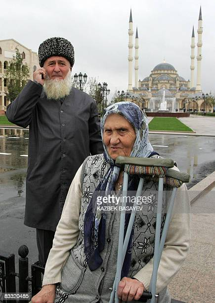 An elderly Chechen couple stands in front of the Ahmad Kadyrov mosque in central Grozny on the day of its official opening on October 17 2008 The...