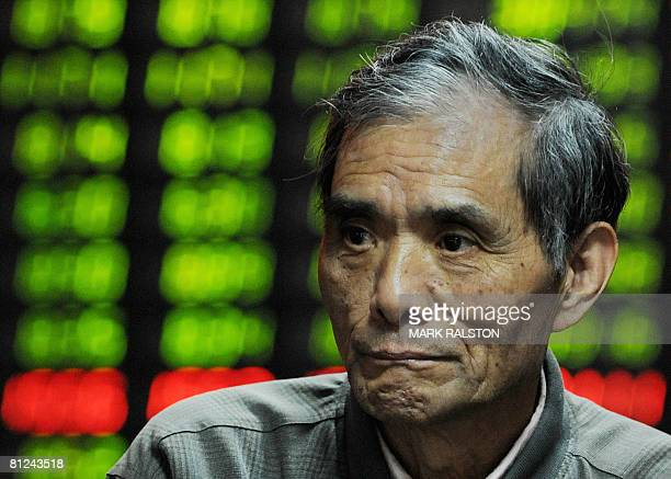 An elderly Chinese investor in front of a stock price board showing the green colouring which indicates falling prices at a private securities firm...