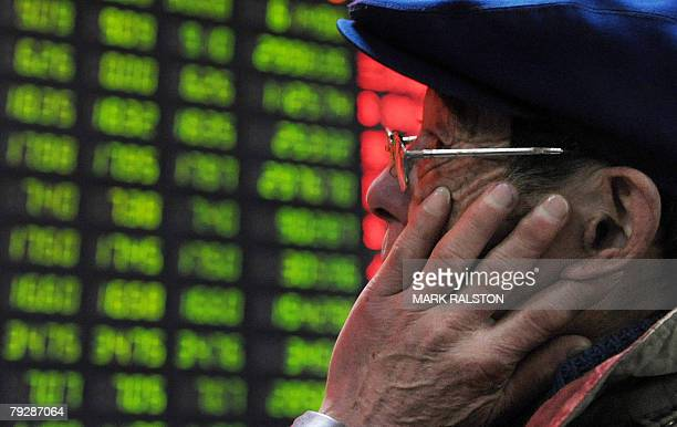 An elderly Chinese investor watches a stock price board showing the green colouring which indicates falling prices at a private securities firm in...