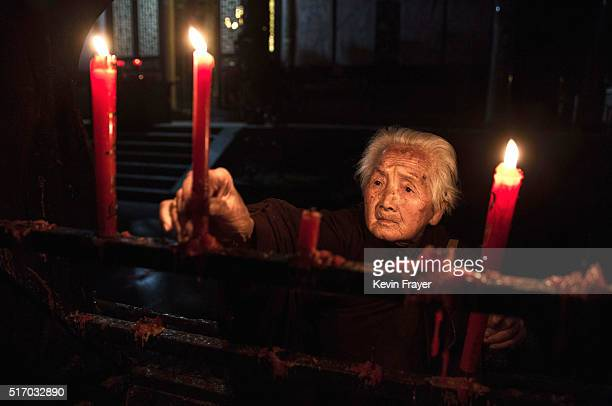An elderly Chinese resident lights candles before morning prayers at the Ji Xiang Temple and nursing home on March 17 2016 in Sha County Fujian...