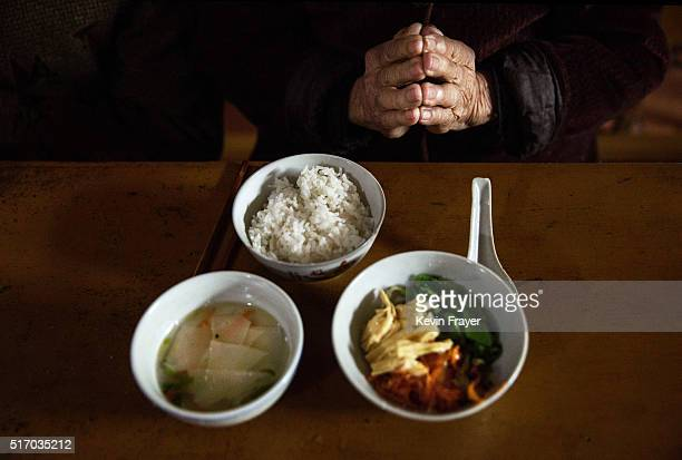 An elderly Chinese resident prays in front of her food during lunch at the Ji Xiang Temple and nursing home on March 18 2016 in Sha County Fujian...