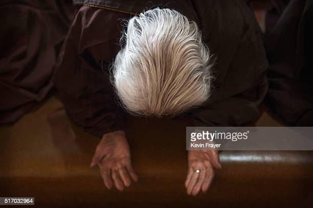 An elderly Chinese woman kneels as she prays during a prayer session at the Ji Xiang Temple and nursing home on March 17 2016 in Sha County Fujian...