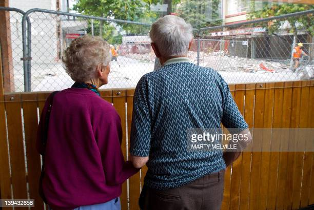 An elderly Christchurch couple watch the demolitional of buildings they grew up with on the other side of a barrier in downtown Christchurch on...