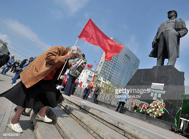 An elderly Communist Party activist carries flowers to Lenin's monument prior to take part in a May Day rallys in the eastern Ukrainian city of...