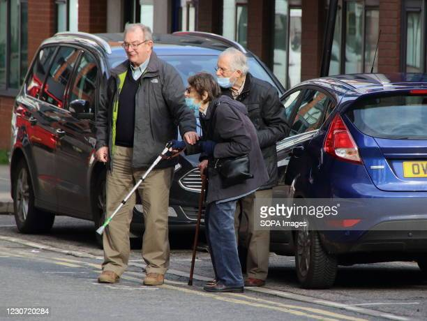 An elderly couple are being helped to cross the road. A steady stream of elderly people with pre-booked appointments at the new Covid-19 Vaccination...