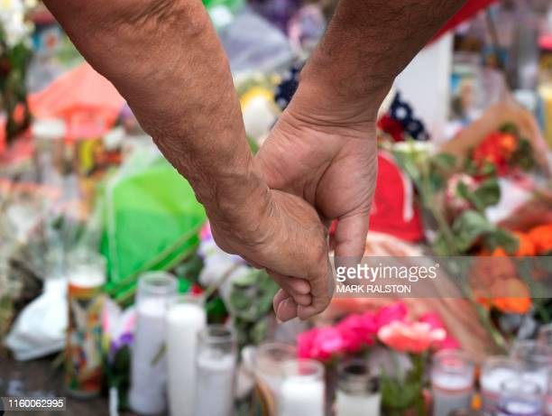 An elderly couple hold hands at a makeshift memorial for shooting victims at the Cielo Vista Mall Walmart in El Paso Texas on August 6 2019 The...
