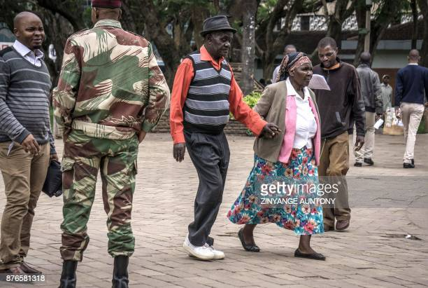 An elderly couple holding hands walk past a soldier in Unity Square in Harare on November 20 2017 Zimbabwe's President faced the threat of...