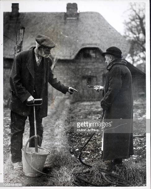 An elderly couple in Ilsley Berkshire trying out their new stirrup pump which will safeguard their thatched cottage in case of fire during World War...