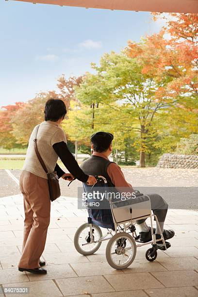 An elderly couple is looking at autumn scenery.