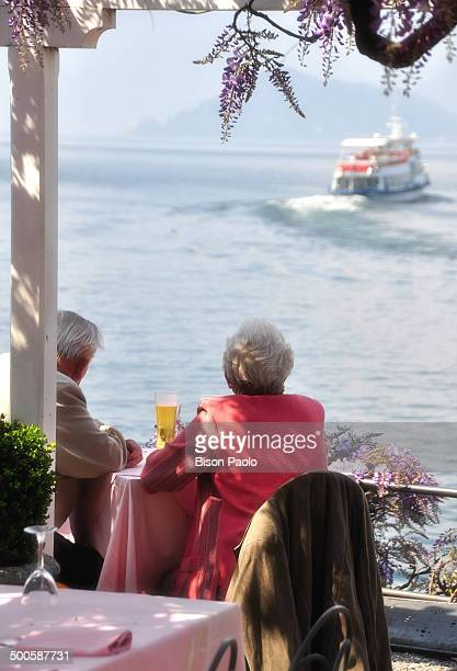 CONTENT] An elderly couple is sitting at a table in a bar on the shore of Lake Como under a wisteria plant They are watching a ferry that crosses the...