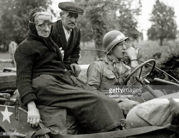 An elderly couple is sitting in a jeep driven by a Military Police wearing a scarf. June 1944. The woman is not on a seat, but on a crat. She wears...