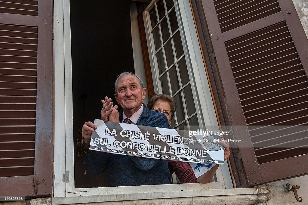 An elderly couple look out of window and hold a banner that translates as 'the crisis is violence on women's bodies' as they watch the students protest during a national general strike against the austerity policy in Europe on November 24, 2012 in Rome, Italy. Students in Italian cities protested against cuts to the education budget and school reforms in the first major student demonstrations since the beginning of the school year. Demonstrators across Italy have been protesting the austerity measures taken by their government in the wake of the Eurozone's financial crisis.