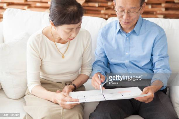 An elderly couple looking at the drawings.