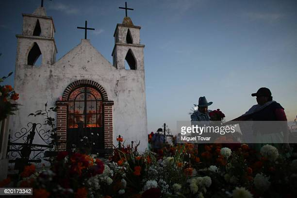 An elderly couple place cempasuchil flowers on a relative grave during during the Day of the Dead celebration known in spanish as Dia de los Muertos...