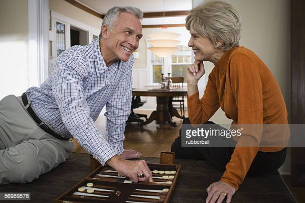 An elderly couple playing a board game