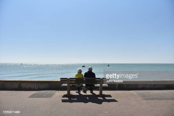 An elderly couple sit and look out at the sea on a quiet promenade during sunny weather during the fifth week of the Coronavirus lockdown on April...