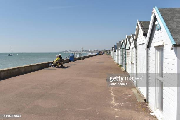 An elderly couple sit and look out at the sea on a quiet promenade during sunny weather on the fifth week of the Coronavirus lockdown on April 22...