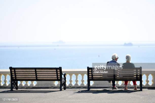 An elderly couple sit in the sunshine on the Hoe promenade overlooking the sea on April 08 2020 in Plymouth England There have been around 50000...
